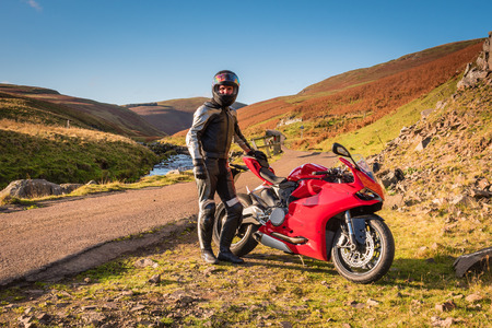 Man and Machine, a red motorbike with rider in Upper Coquetdale, Northumberland on a sunny day