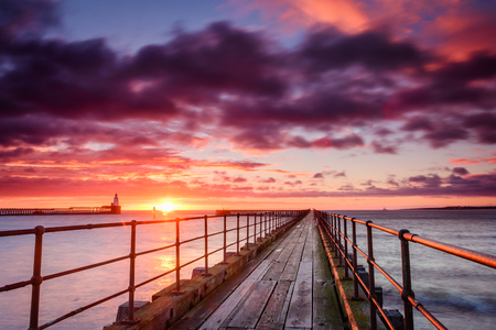 Sunrise at River Blyth Harbour, as the river reaches the North Sea between the piers in Northumberland