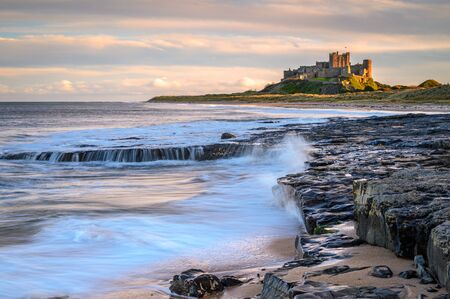 Bamburgh Beach below the Castle, and dunes which are dominated by the imposing medieval castle and located within Northumberland Coast Area of Outstanding Natural Beauty Stock Photo