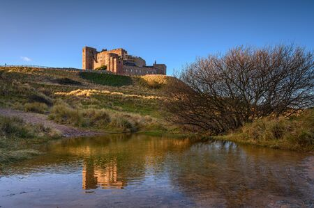 Floodwater in Bamburgh Beach Dunes, which are dominated by the imposing medieval castle and located within Northumberland Coast Area of Outstanding Natural Beauty Stock Photo