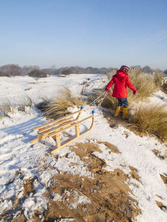 small girl in colourful winter clothing  pulling a wooden sledge to the top of the hill in a snow covered dune landscape Stock Photo - 17289049
