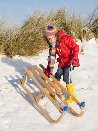 small girl in colourful winter clothing playing with a wooden sledge  in a snow covered dune landscape Stock Photo - 17289046