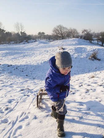 small boy in winter clothing pulling a wooden sledge to the top of the hill in a snow covered dune landscape Stock Photo - 17289045