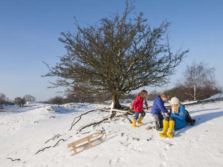 snow break: Two colourfully dressed young children and mother, taking a break in a snow covered dune landscape