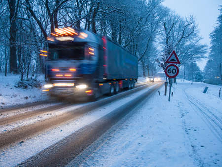 fast moving heavy goods vehicle passes a warning sign in a snow storm under morning light Stock Photo - 17670779