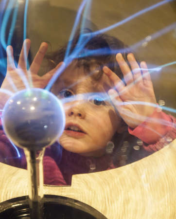 small girl touches a plasma ball with her hands and watches the electrostatic discharge Stock Photo - 17567412