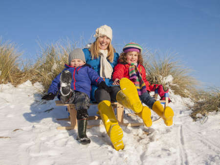 portrait of mother, small boy  and small girl in colourfull winter clothing sitting on a wooden sledge photo