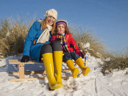 portrait of mother and small girl in colourfull winter clothing sitting on a wooden sledge photo