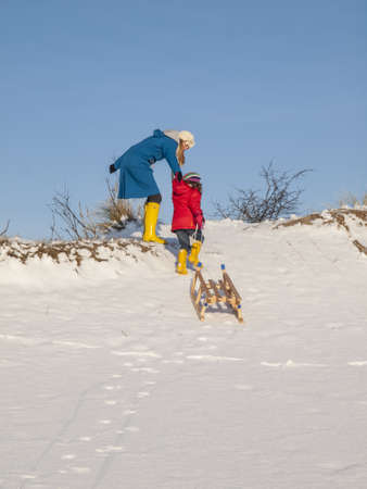 togther: mother helps small girl pull  a wooden sledge to the top of a snow covered hill Stock Photo