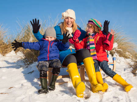 Portrait of two young children and mother, colourfully dressed, smiling and waving in a snow covered dune landscape. photo