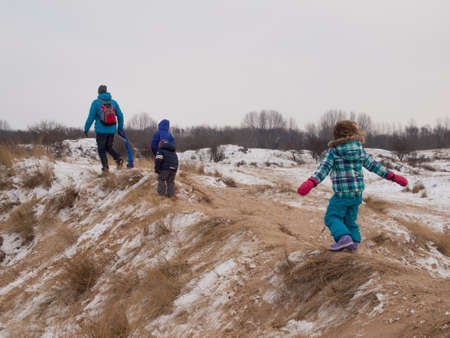 togther: small children walking with dad over dune tops in a winter dune landscape