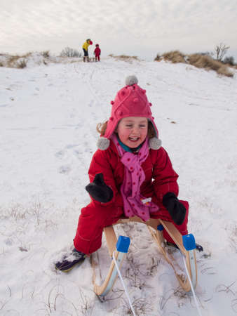 togther: portrait of small girl wearing winter clothing sitting on a sledge laughing in a winter landscape