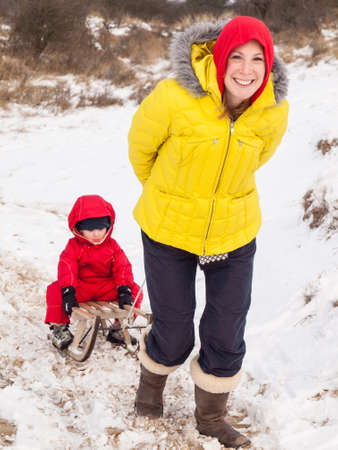 togther: smiling mother in colourful winter clothes pulls small boy in red winter suit on a wooden sledge through snow covered dunes Stock Photo