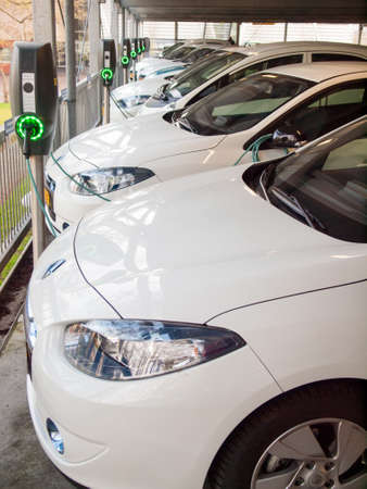 electric vehicles being recharged at a row of charging stations