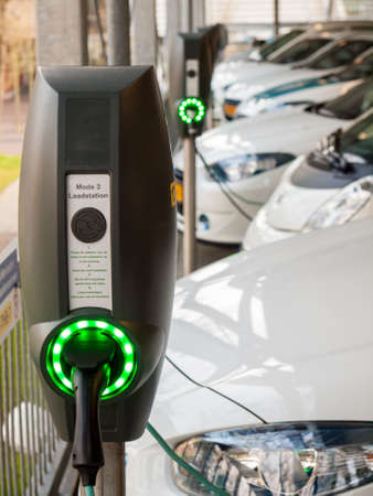 row of charging stations with electric vehicles being recharged