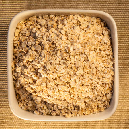 glycemic: porridge oats,  a low glycemic index food, in a square bowl, viewed from above Stock Photo