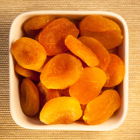 glycemic: dried apricots,  a low glycemic index food, in a square bowl, viewed from above Stock Photo