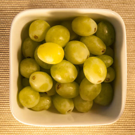 glycemic: green grapes,  a low glycemic index food, in a square bowl, viewed from above