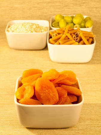dried apricots a low glycemic index food in a bowl with a selection of other low glycemic foods in the background photo