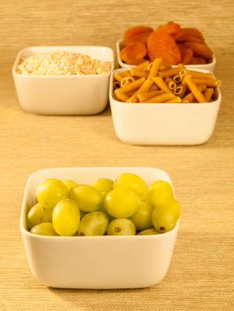 glycemic: dried apricots a low glycemic index food in a bowl with a selection of other low glycemic foods in the background