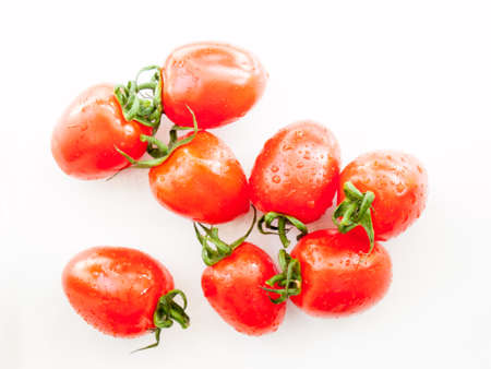 preperation: ripe red plum tomatoes  covered in water droplets on a white background
