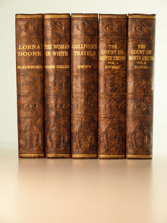 the count of monte cristo: old books in a row with titles visible  classic titles in the public domain for which copyright has expired  Stock Photo