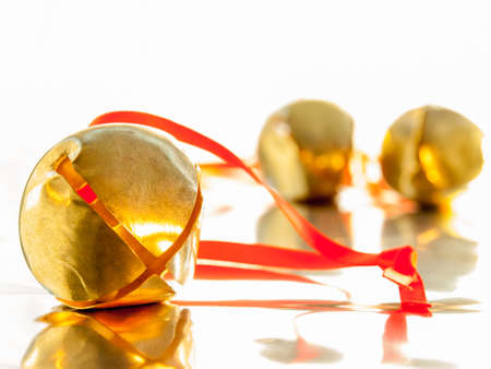 shiny golden  sleigh bell with red ribbon tie on reflective surface with sleigh bells out of focus in background photo
