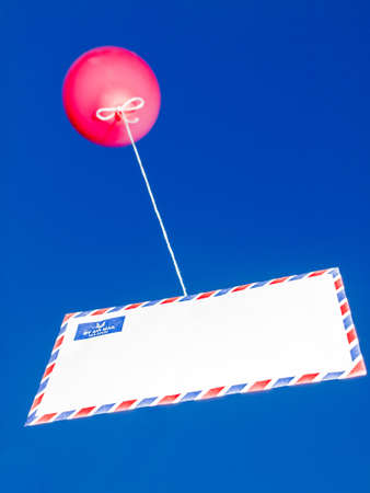 communication concept red balloon attached to an airmail envelope by a string against a bright blue sky photo