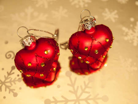 diamond shaped: two heart shaped diamond studded christmas baubles  on a reflective surface with snow flakes