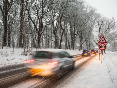 bad weather: fast moving car brakes as it passes a speed restriction sign in a snow storm under morning light