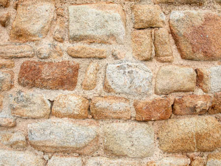 masonary: aged and weathered old red sandstone wall Stock Photo