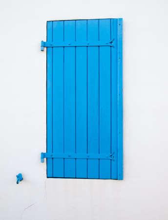 mediteranean: bright blue window shutter against a white wall
