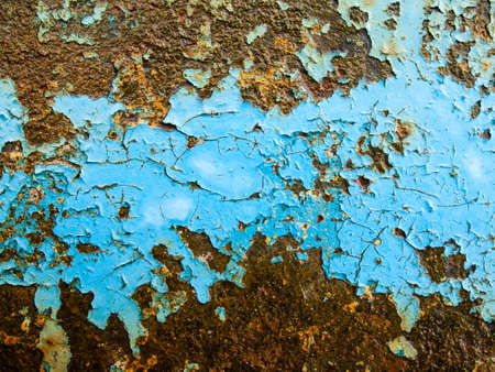 flaking blue paint on wet rusty red iron background texture photo