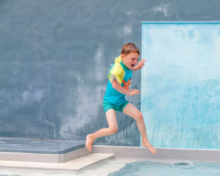 small boy in armbands jumping into an outdoor swimming pool photo