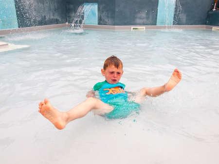 agachado: pequeño niño jugando en una piscina al aire libre