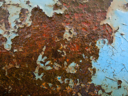 flaking: background of aged flaking blue paint on wet rusty iron