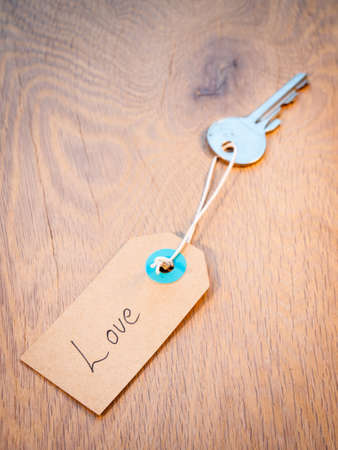 finding love: old key on a string with retro brown paper label reading love  Secret to finding love concept  Stock Photo