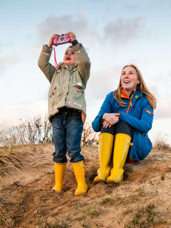 togther: middle aged woman and  small girl  in winter clothing and rubber boots playing togther in  a sunny autumn dune landscape