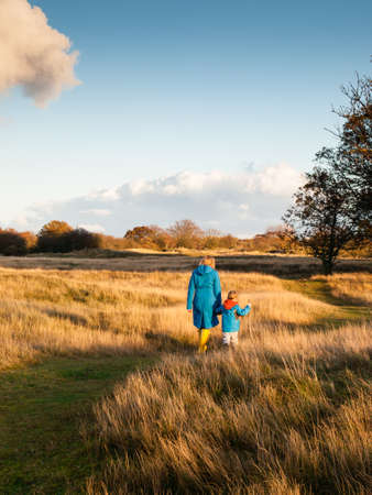 togther: woman and small boy walk hand in hand in a sunny autumn dune landscape