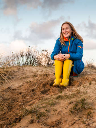 portrait of middle aged woman  in winter clothing and rubber boots in  a sunny autumn dune landscape photo