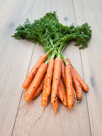 Bunch of Freshly harvested carrots on aged wooden background photo