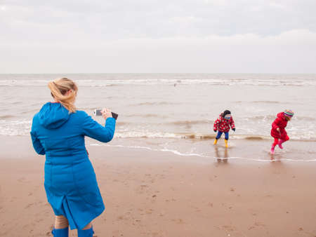 woman photographing  small boy and girl in winter clothing and rubber boots on a winter beach with a smart phone photo