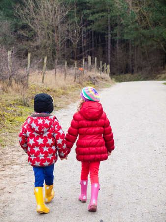 small boy and girl in winter clothing walking hand in hand along a path througha wooded landscape photo