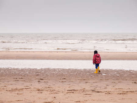 small boy in winter clothing and rubber boots on a winter beach photo