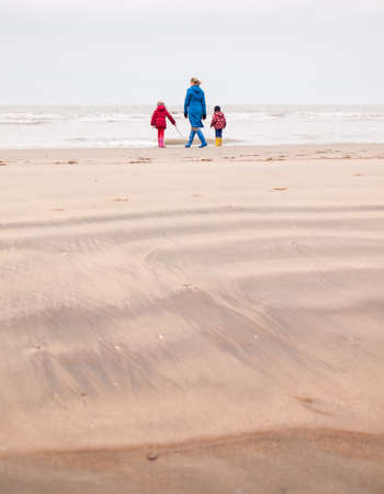 woman with small boy and girl in winter clothing and rubber boots on a winter beach looking out to sea photo