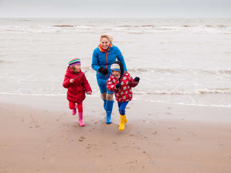 woman with small boy and girl in winter clothing and rubber boots playing on a winter beach running away from waves photo