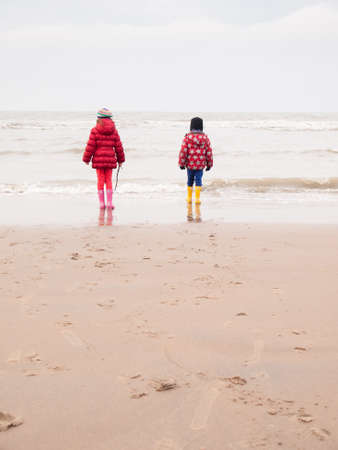 small boy and girl in winter clothing and rubber boots on a winter beach looking out to sea photo