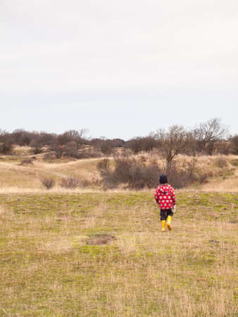 small boy  in winter clothing and rubber boots on a winter day walking alone through a dune landscape photo