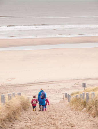 woman with small boy and girl in winter clothing and rubber boots walking down to a winter beach along a dune path photo