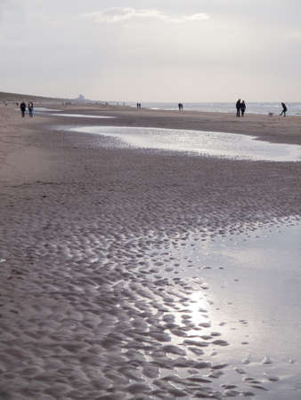 togther: view along a north sea beach on a winters day with people walking under stormy grey skies
